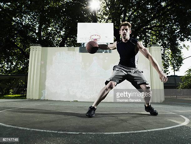 male basketball player dribbling ball on outdoor c - ドリブル ストックフォトと画像
