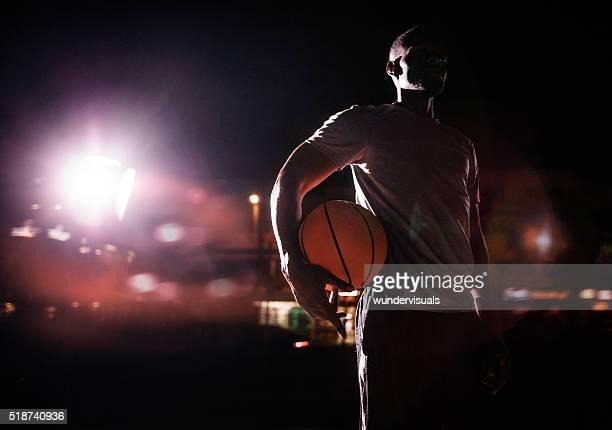 Giocatore di basket maschile con palla sul fianco di sera