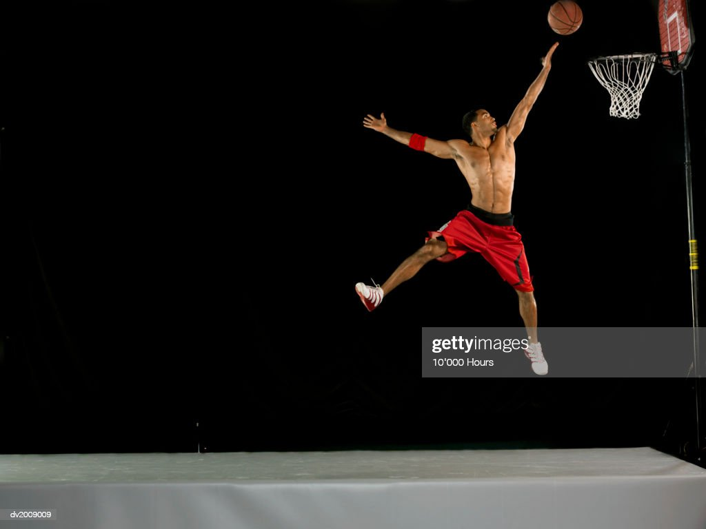 Male Basketball Player in Mid Air and Aiming for the Hoop, Studio Shot : Stock Photo