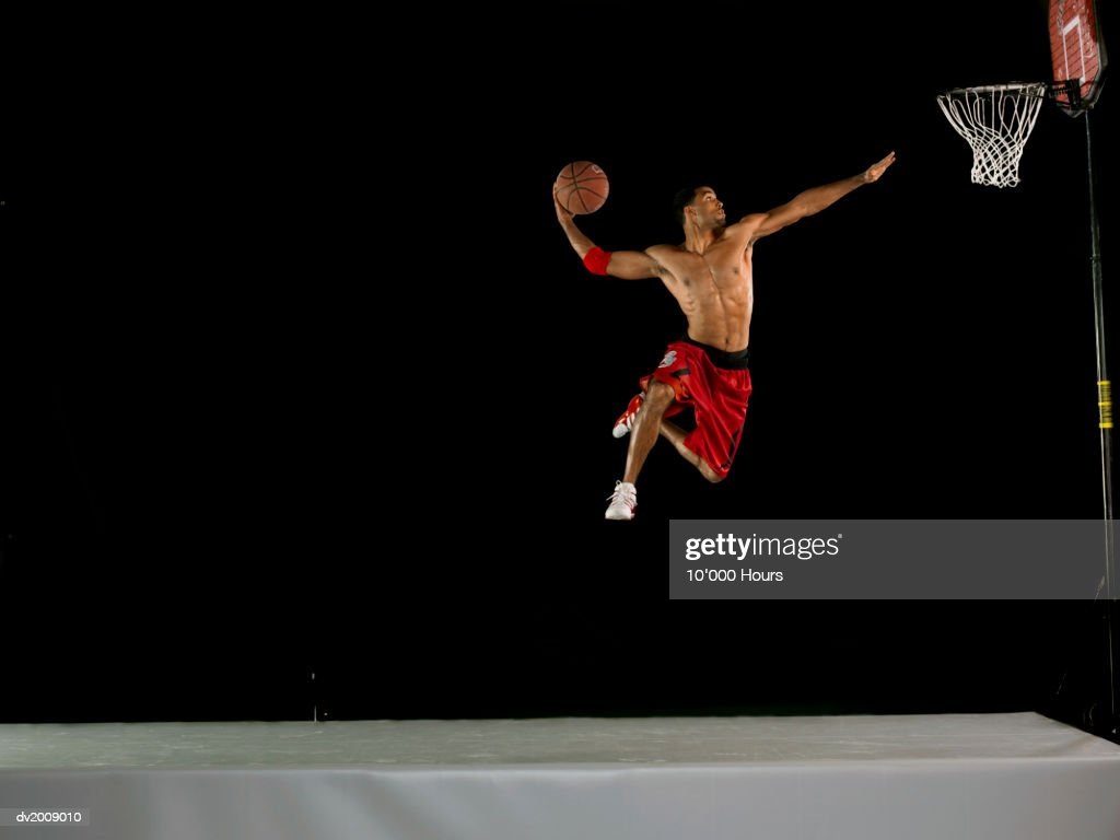 Male Basketball Player Jumping in Mid Air and Aiming for the Hoop, Studio Shot : Stock Photo