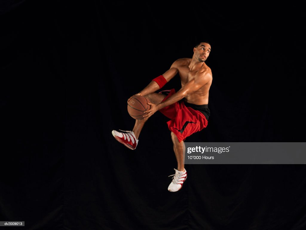 Male Basketball Player Jumping Mid Air Holding a Basketball : Stock Photo