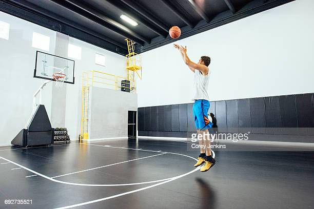 Male basketball player jumping to throw ball in basketball hoop