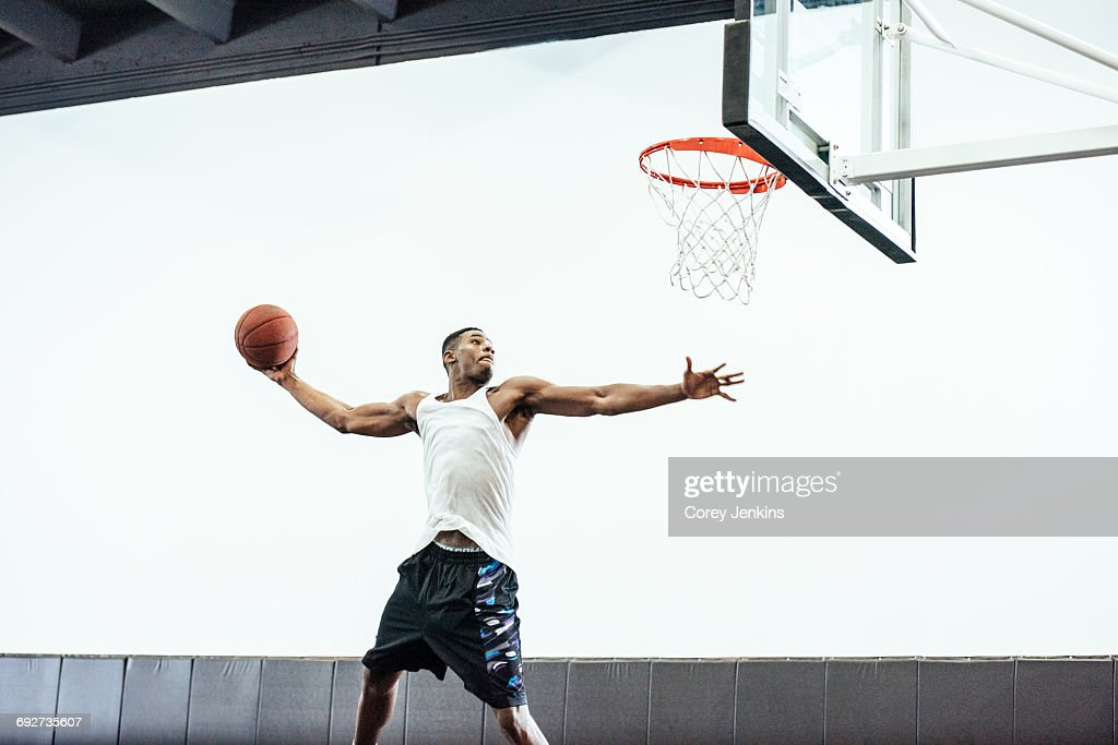 Male basketball player jumping to throw ball in basketball hoop : Stock Photo