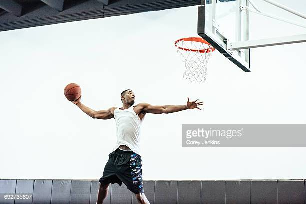 male basketball player jumping to throw ball in basketball hoop - marquer photos et images de collection