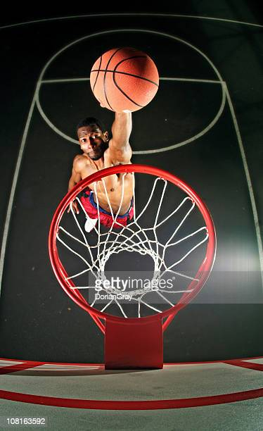 Male Basketball Player on Court Jumping Up to Dunk