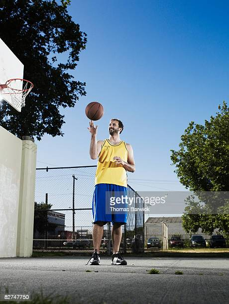 Male basketball player on outdoor court spinning b
