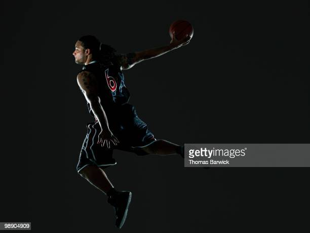 male basketball player preparing to dunk ball - studio shot stockfoto's en -beelden