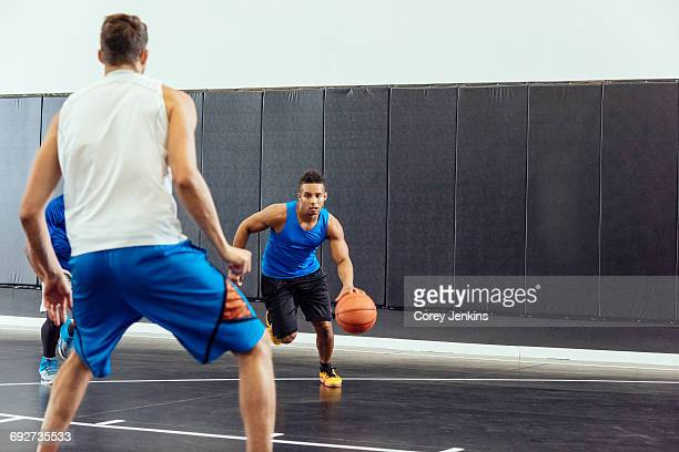 Male basketball player running with ball in basketball game