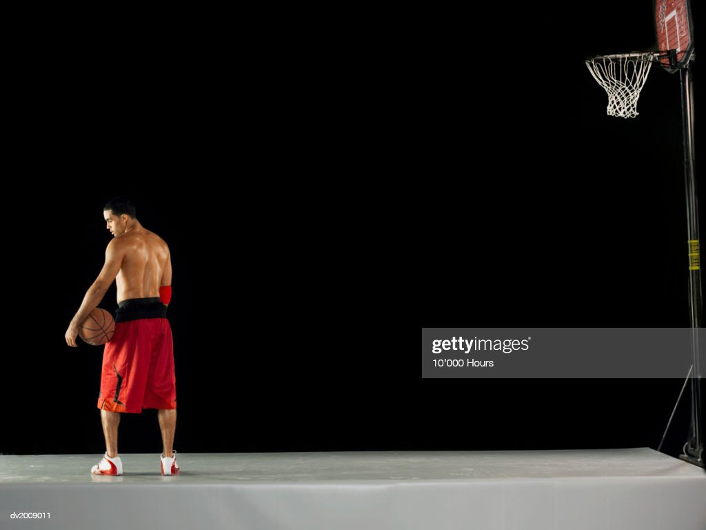 Male Basketball Player Standing in a Studio Set up as a Basketball Field : Stock Photo