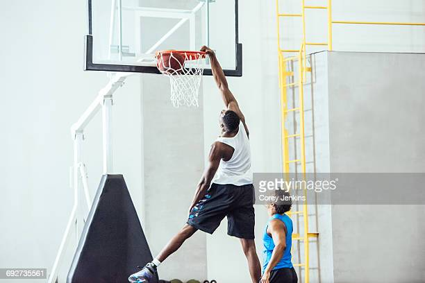 male basketball player throwing ball into hoop on basketball court - segnare foto e immagini stock