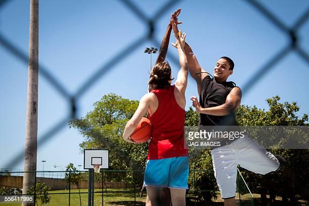 Male basketball team having high five on basketball court
