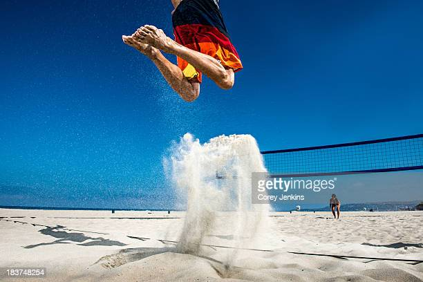 Male beach volleyball player jumping mid air