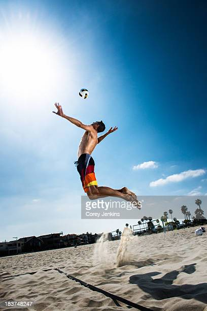 Male beach volleyball player jumping mid air to hit ball
