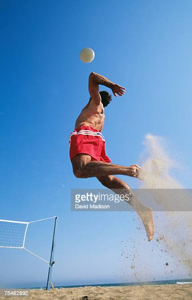 Male beach volleyball player jumping up to spike ball. California, USA.
