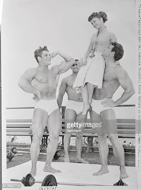 Male beauty contest winner Dick Dubois who doesn't have time for dates shown flexing his biceps for MGM star Debbie Reynolds while filming Athena...