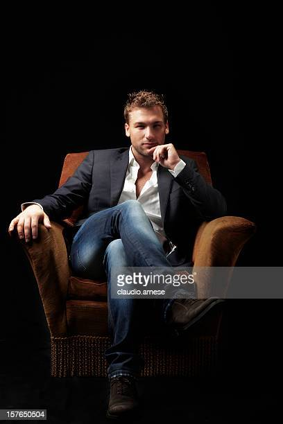 male beauty sitting on armchair. color image - armchair stock pictures, royalty-free photos & images
