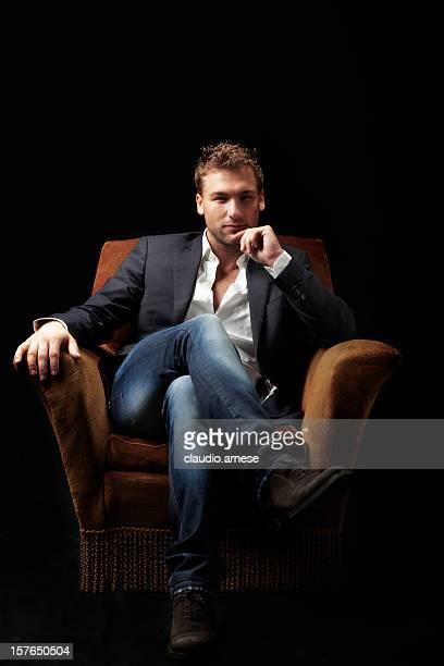 male beauty sitting on armchair. color image - armstoel stockfoto's en -beelden
