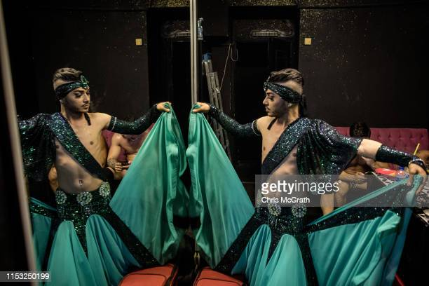 """Male belly dancer Segah prepares before going on stage at a nightclub on June 02 2019 in Istanbul Turkey Male belly dancers or """"zennes"""" date back to..."""