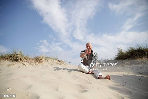 Male Best Ager sitting in the dunes at the North Sea in De Haan, Belgium, Europe