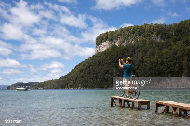 male bicyclist dock mountain lake - bariloche stock pictures, royalty-free photos & images