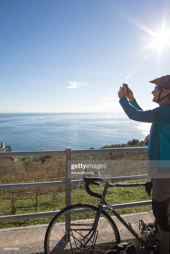 Male bicyclist takes smart phone pic from road, to sea : Stock Photo