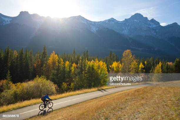 a male bike commuter rides the trans canada trail bike path near canmore, alberta, canada in the fall. - clear sky stock pictures, royalty-free photos & images