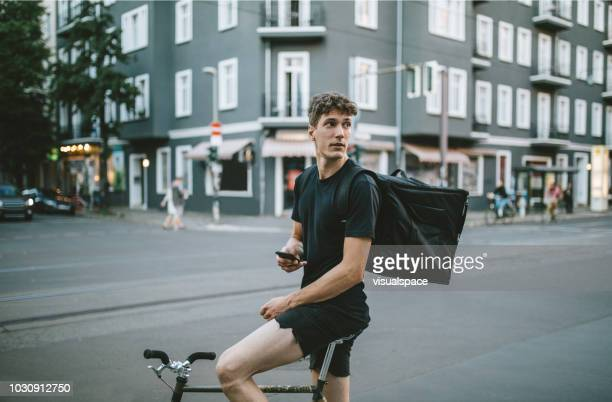 male bike courier checking his phone. - bicycle messenger stock pictures, royalty-free photos & images