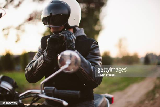male biker adjusting helmet while sitting on motorcycle - crash helmet stock pictures, royalty-free photos & images