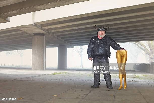 male biker holding gold mannequin legs - gold pants stock photos and pictures