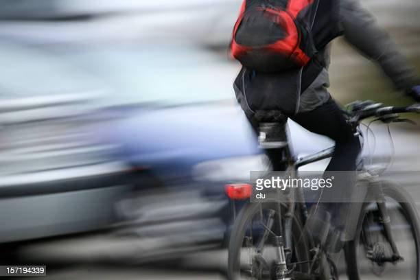 Male biker passing by in rush hour