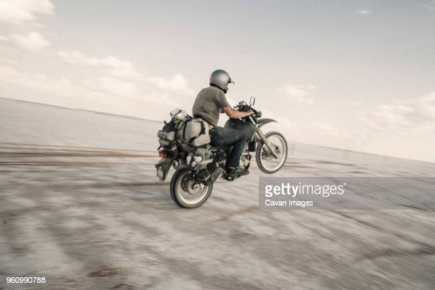 male biker riding motorbike on desert road against sky - ecchi biker stock pictures, royalty-free photos & images