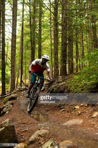 male biking through a lush forest - mountain biking stock pictures, royalty-free photos & images
