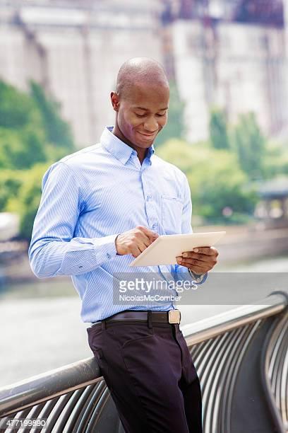 Homme noir employé de bureau consulter des rapports sur la tablette à l'extérieur