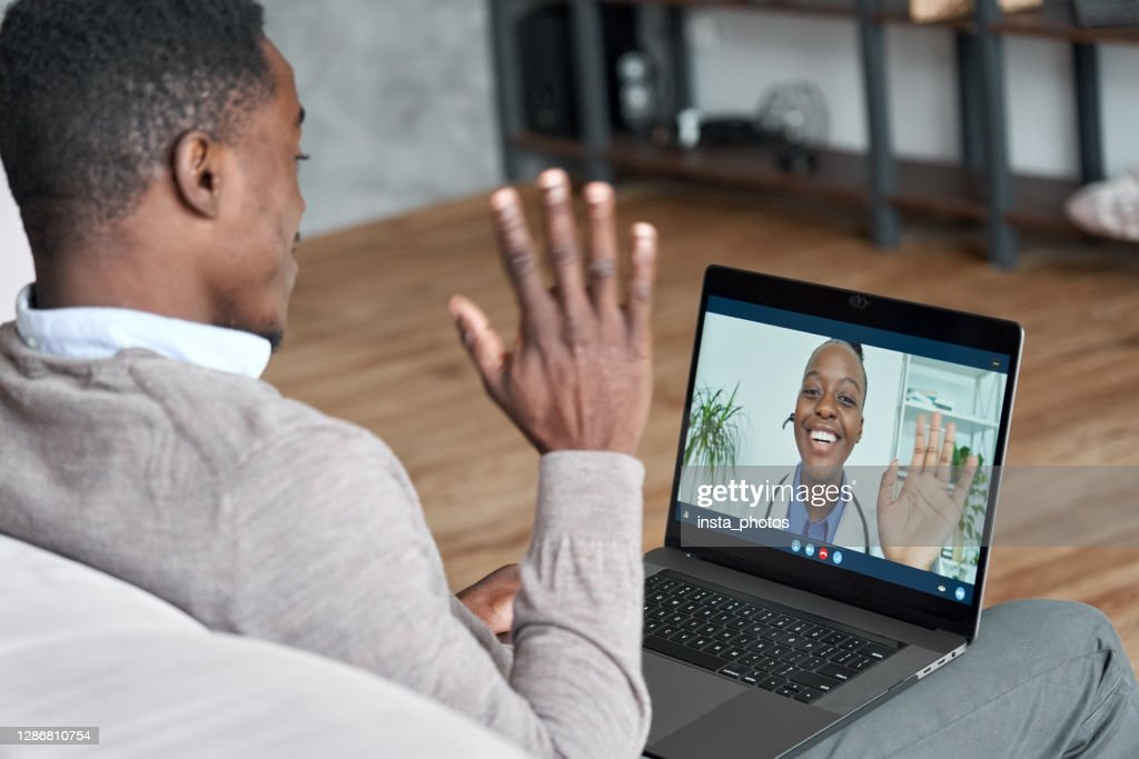 Male black patient talking on conference video call to female african doctor. Virtual therapist consulting young man during online appointment on laptop at home. Telemedicine chat, telehealth meeting : Stock Photo