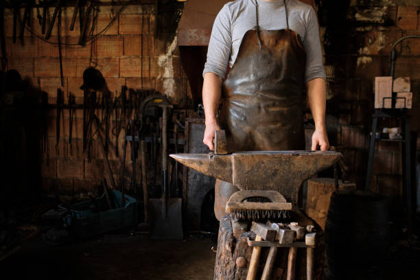 Male blacksmith standing with hammer by anvil at shop