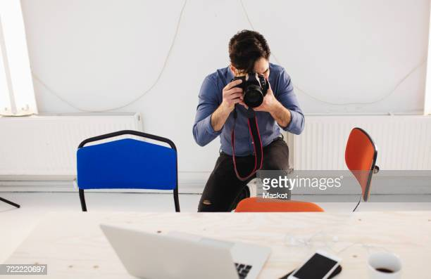 Male blogger photographing desk in creative office