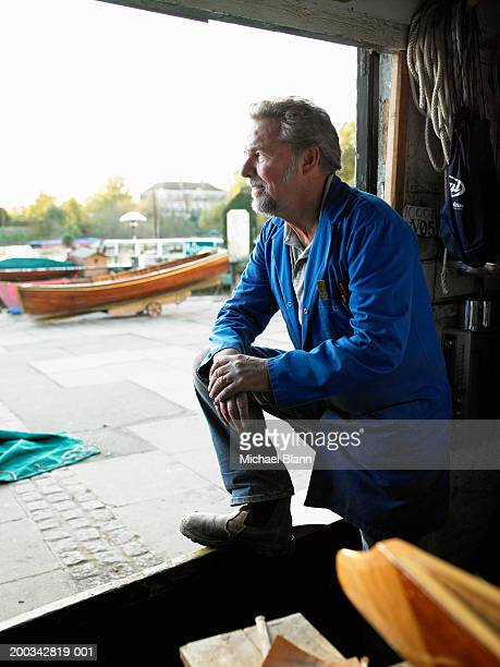Male boat builder looking out of workshop, smiling, side view