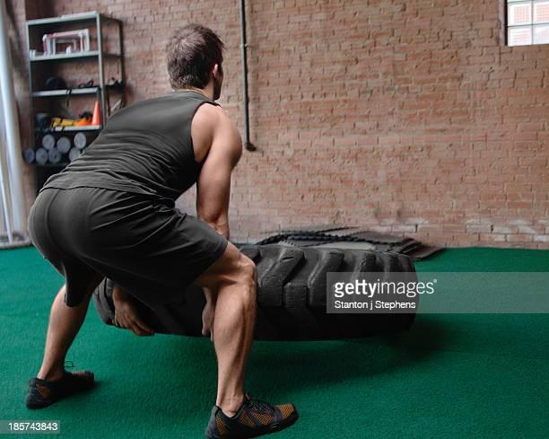 male bodybuilder lifting tyre - ランニングショートパンツ ストックフォトと画像