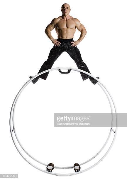 Male bodybuilder posing on top of German wheel