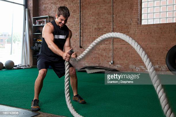 Male bodybuilder using ropes in gym