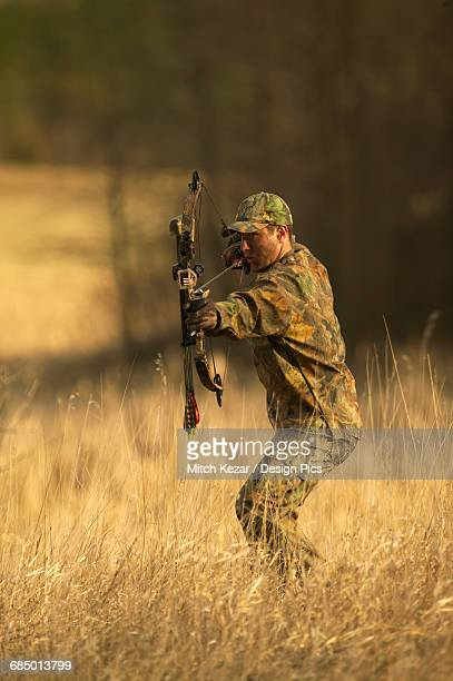 male bowhunter draws bow while turkey hunting - turkey hunting stock photos and pictures