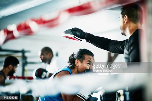 Male boxer ducking during training session with trainer in boxing ring