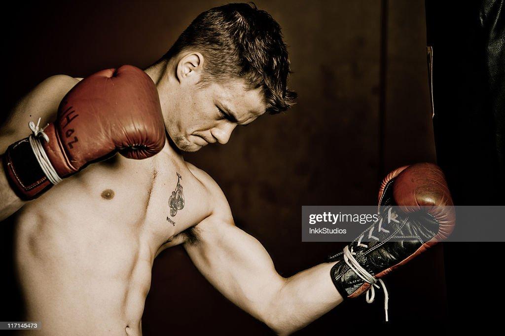 Male boxer hitting the bag : Stock Photo