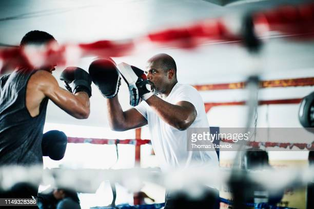 male boxer holding up punch mitts for partner while training in boxing ring - boxen sport stock-fotos und bilder