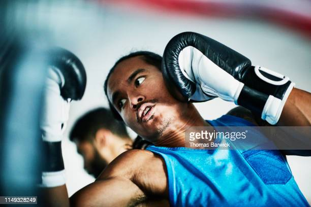 Male boxer shadow boxing while warming up for workout in boxing gym