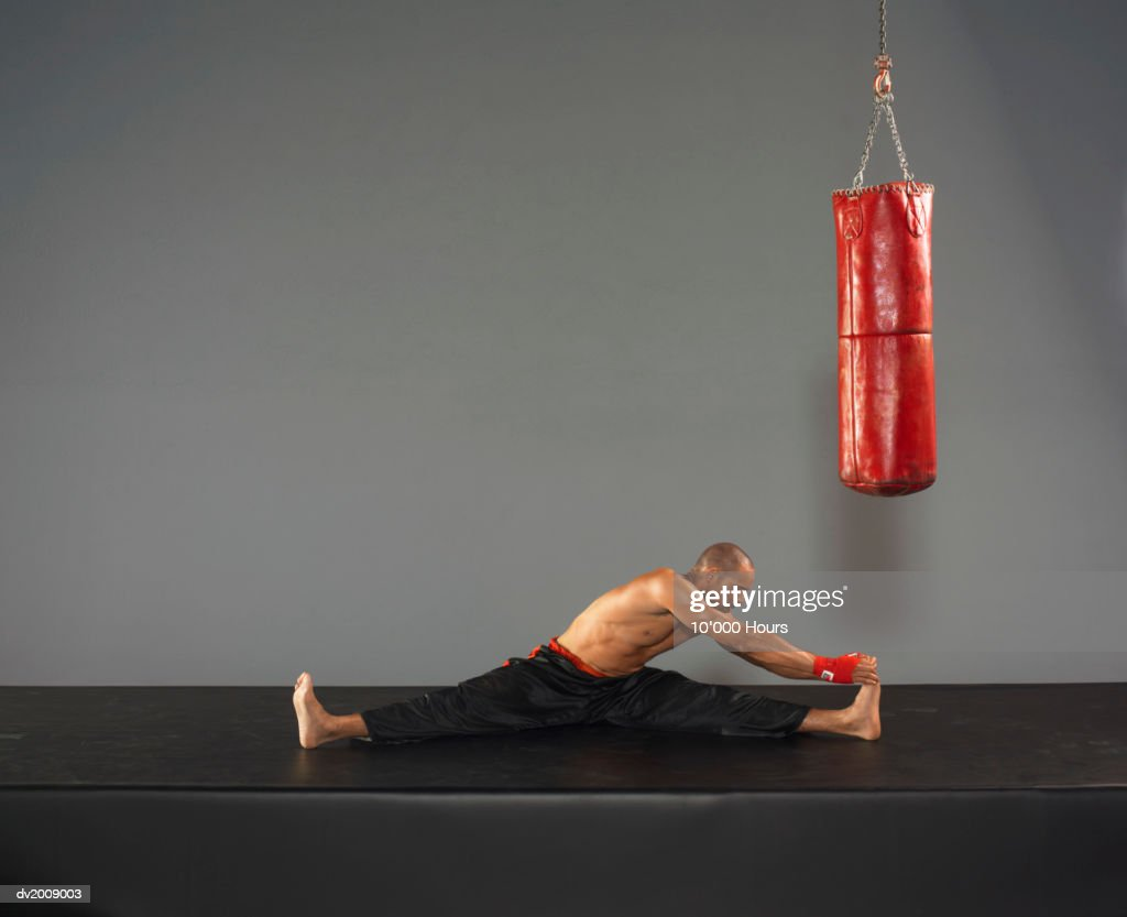 Male Boxer Stretching Next to a Punch Bag : Stock Photo