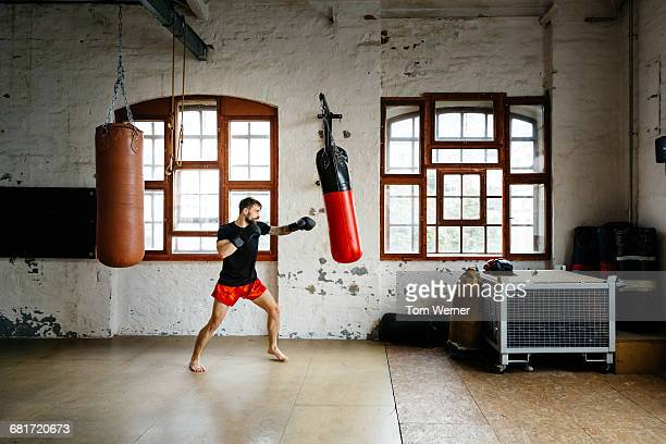 Male boxer training on sandbag in a gym