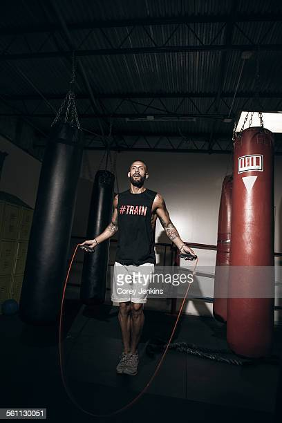 Male boxer training on skipping rope in gym