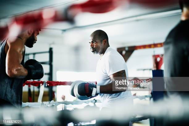 Male boxer training with partner in boxing ring in gym