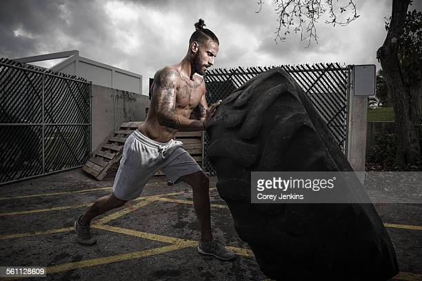 Male boxer training with truck tyre in yard